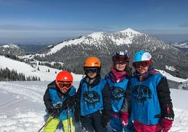 Four ski students at their kids ski lessons (3 to 14 years) for all levels with the Snowcamp Martina Loch ski school in the Spitzingsee ski area.