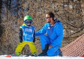 Un moniteur de Ski Connections explique tranquillement à un jeune skieur comment faire un chasse-neige lors d'un cours de ski pour enfants de 3 à 5 ans à Serre-Chevalier.