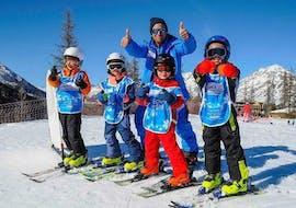 Quatre apprentis skieurs et leur moniteur de Ski Connections passent du bon temps sur les pistes lors d'un cours de ski pour enfants à Serre-Chevalier.