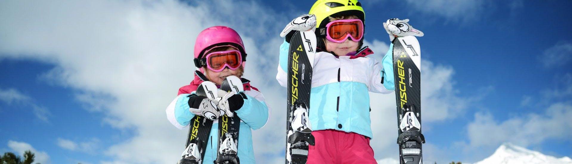 Zwei Mädchen warten auf den Beginn ihres Kinder-Skikurses für Anfänger mit der Skischule Ruhpolding im Skigebiet Westernberg.