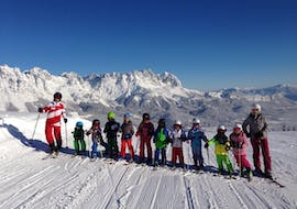 A group of children at their kids ski lessons  (3 to 14 years) for advanced skiers with their ski instructors from the Ski School Ellmau Hartkaiser.