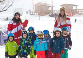 A group of children at the kids ski lessons  (3 to 14 years) for beginners with their ski instructors from the Ellmau Hartkaiser Ski School.