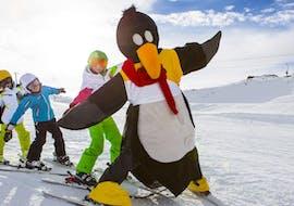 Die Kinder haben Spaß mit dem Pinguin Bobo beim Kinder-Skikurs für Anfänger mit der Skischule Ruhpolding im Skigebiet Westernberg.