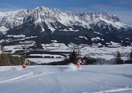 Two ski instructors from the Ski School Ellmau Hartkaiser skiing down the piste in the beautiful Ellmau ski area.