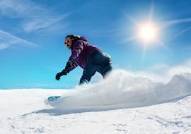 A snowboarder gliding down the slopes with the Ski School Ellmau Hartkaiser as part of the private snowboarding lessons for all levels & ages.