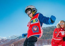 """Under the supervision of a ski instructor from the ski school ESF Ski School Val d'Isère, a child makes great progress on skis during the Kids Ski Lessons """"Max 8"""" (5-12 years) - Advanced."""