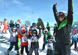 A ski instructor with the children at the kids ski lessons Bambini (3-4 y.) for beginners with the Tiroler Ski School Aktiv Brixen im Thale.