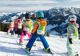 Children follow their ski instructor at the kids ski lessons (4 - 15 years) for beginners with the Tiroler Ski School Aktiv Brixen im Thale.