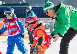 During the Kids Ski Lessons (4-12 y.) - All Levels - Half Day, a small boy takes the first steps on skis under the supervision of a ski instructor from Skischule Snow & Bike Factory Willingen.