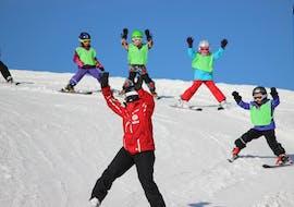 Un groupe d'enfants apprend à skier avec leur moniteur de ski de la Schweizer Skischule Zweisimmen pendant leurs cours de ski enfants (3-16 ans) pour débutants.