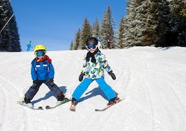 Two children are skiing down a slope in plough position during Kids Ski Lessons (6-15 years) for Advanced skiers, with the ski school Kahler Asten.