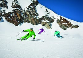 Three skiers are riding down a slope during their private ski lessons for adults of all levels with ski school Dachstein West in Gosau.