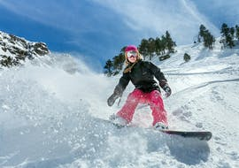 A snowboarding going down a slope during private snowboarding lessons for kids and adult with ski school Dachstein West in Gosau.