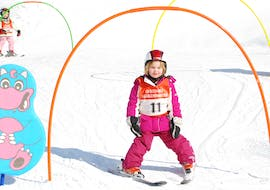 """A small child skiing during her kids ski lessons """"Zwergerl"""" for beginners with skischule Heugenhauser Saalbach."""