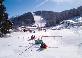 """The children play together in the beautiful Kinderland in the snow during the kids ski lessons """"BOBOs Kinderclub"""" (4-14 years) - beginner of the Ski School Fieberbrunn Widmann Mountain Sports."""