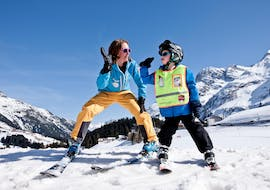 An instructor is giving a kid a high-five during his private ski lessons for kids of all levels with ski school Warth in Warth-Schröcken.