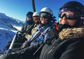 Un groupe de snowboardeurs sourient à l'appareil photo tandis qu'ils empruntent les remontées mécaniques pour rejoindre leurCours de snowboard - Tous âges - Après-midi - Débutant avec l'école de ski ESI Easy2Ride Morzine.