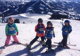 """Four kids during their kids ski lessons """"Bambini"""" for all levels with skischool Söll Hochsöll Embacher."""