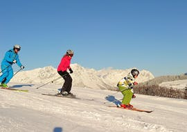 Two skiers riding down a slope with their instructor during their adult ski lessons for beginners with skischool Söll Hochsöll Embacher.