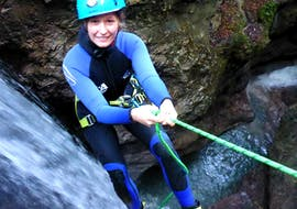 """A woman abseiling down a waterfall at her Canyoning Tour """"Narrow Aquasplash"""" at Taxaklamm under the instruction of the experienced team of CIA Canyoning in Austria & more Adventures."""