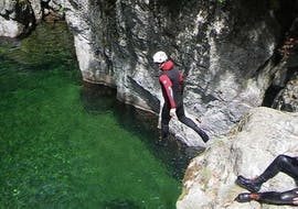 A man is jumping in an emerald pool during his Classic Canyoning in Canyon Aéro Besorgues with Geo Ardèche Canyon.