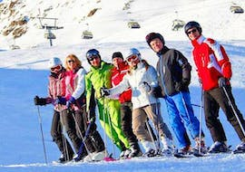 A group of participants of the Ski Lessons for Teens & Adults - All Levels organized by the ski school Ski- and Bike School Ötztal Sölden in the ski area of Ötztal in Sölden is smiling at the camera on a snowy slope.