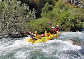 During the Rafting on the Cetina River with City-Transfer from Split, two girls are facing the rapids of the river together with their experienced guide from Adventure Dalmatia.