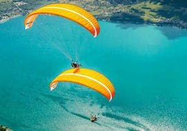 A couple is enjoying the Tandem Paragliding in Lake Annecy - Discovery activity with Flyeo.