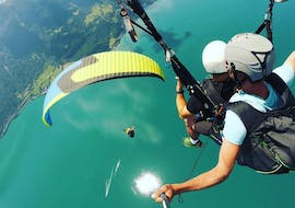 """A tandem pilot and his passenger are flying over the turquoise Lake Thun during the Tandem Paragliding """"The Sensational"""" in Interlaken with Twin Paragliding."""