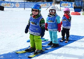 """Three kids are practicing in the kindergarten during the Kids Ski Lessons """"Bolgen"""" (4-7 y.) for First Timers for Intermediates with the swiss ski school of Davos."""