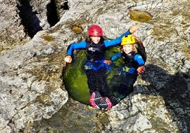 2 kids lying in a natural water pool on their canoying tour in Almbach with Torrent Outdoor Experience.
