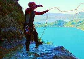A guide from Torrent Outdoor Experience is preparing an abseiling passage during the Ultimate Canyoning in the Altersbach with a view of the Mondsee.