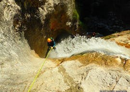 """A man abseiling down a waterfall on his Canoying """"Vertical"""" Tour in Fischbach with Torrent Outdoor Experience."""