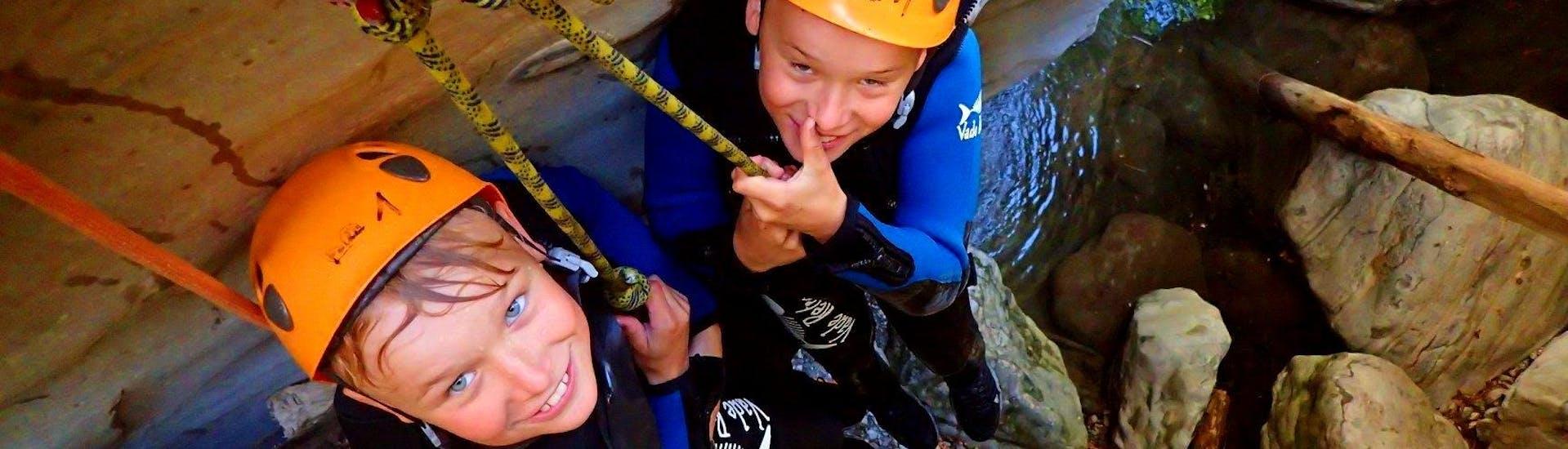 Zwei Kinder werden beim Canyoning im Torrente San Michele - Family Fun, das von Skyclimber organisiert wird, zum Wasser geführt.