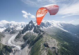 A paragliding pilot from Kailash Paragliding is doing a Tandem Paragliding Flight from Planpraz - Chamonix above stunning mountain scenery in summer.