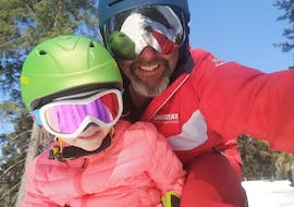 A ski instructor from the Lermoos Snowpower ski school with a young child during a private ski lessons for kids of all levels.