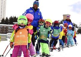 Un groupe d'enfants s'amuse avec le moniteur de ski de l'école de ski Scuola di Sci Olimpionica lors d'un Cours de ski Enfants (5-12 ans) pour Confirmés - Vacances dans la station de ski de Via Lattea à Sestriere.