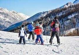 Un groupe de jeunes skieurs écoutant attentivement le moniteur de ski pendant les Cours de ski Enfants (5-12 ans) pour Débutants organisées par l'école de ski YES Academy Sestriere à Sestrières.