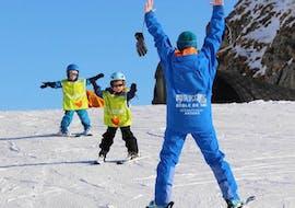 Un moniteur de l'ESI Glycérine encourage des jeunes skieurs durant leurs premiers chasse-neige lors d'un cours de ski pour enfants à Anzère.