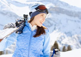 A skier carries her skis to join her private ski lesson with the ESI M3S Morgins.