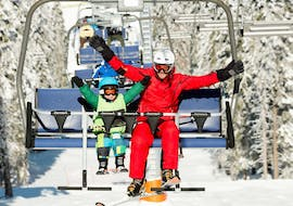 A young skier and his instructor from the ESI MRS Morgins take the chairlift together during a private ski lesson for kids.