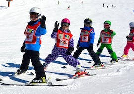 Happy children are waving at the camera as they practice skiing during the Kids Ski Lessons (from 3 years) - All Levels with Skischule Kitzbühel Rote Teufel.