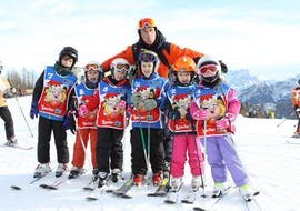 Kids taking a picture with the ski instructor in Falcade after one of the Kids Ski Lessons (4-12 y.) for All Levels.