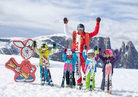 A group of kids having fun on the snow with their instructor with Scuola di Sci Alpe di Siusi.
