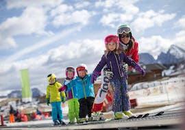 People having fun on the snow during the kids ski lessons for intermediates with Scuola di Sci Alpe di Siusi.