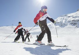 A row of children skiing during their kids ski lessons for first-timers in Stubai.