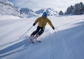 A man descends a slope during a private ski lesson for adults with Escuela Ski Baqueira.