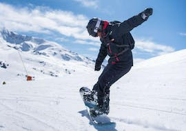 A student practices snowboarding during a private ski lesson for all levels and anges with Escuela Ski Baqueira.