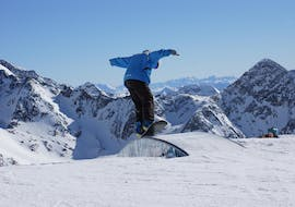 A snowboarder is learning some tricks in the fun park during snowboarding lessons for adults with ski school Neustift Olympia at Stubai glacier.