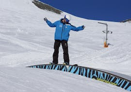 A snowboarder is learning some tricks in the fun park during private snowboarding lessons with ski school Neustift Olympia at Stubai glacier.